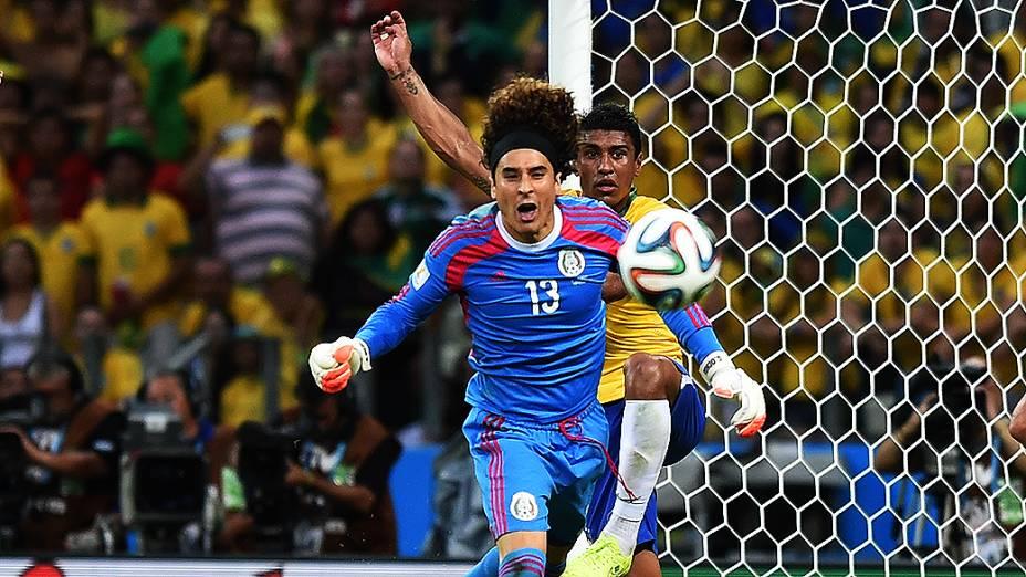 O goleiro Guillermo Ochoa em lancecom Paulinhono jogo contra o Brasil
