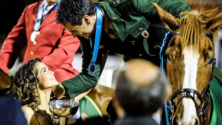 Competição de cavalos de Theo (Rodrigo Lombardi), que estende a taça para a Morena (Nanda Costa)