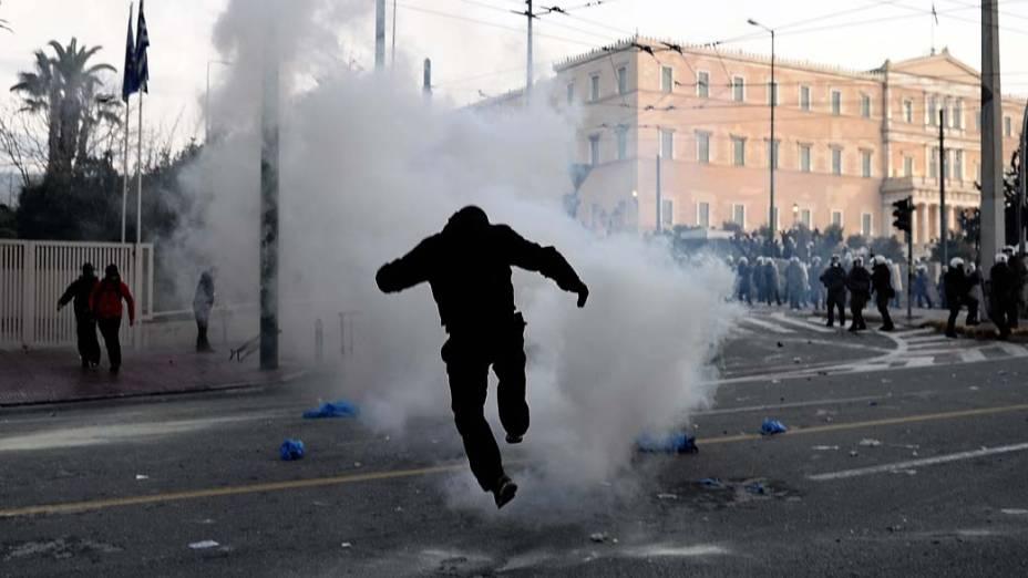 Manifestante chuta bomba de gás lacrimogêneo em confronto com a polícia em frente ao Parlamento grego, 12/02/2012