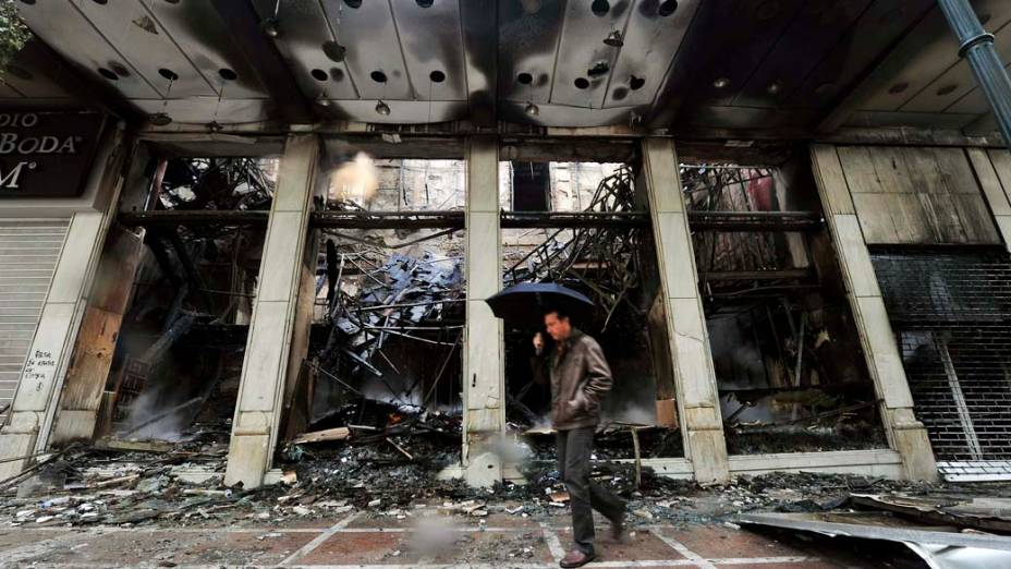 Homem passa em frente a loja incendiada em Atenas, após noite de violência devido à aprovação de um novo pacote de austeridade econômica