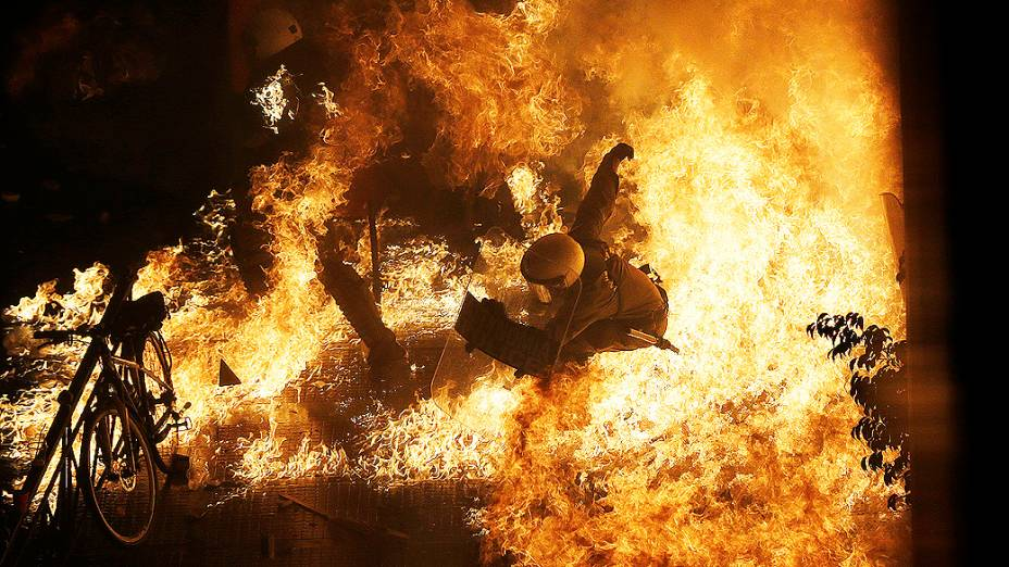 Policial é atingido por chamas de uma bomba de gasolina jogada por manifestantes em frente ao parlamento, durante confrontos em Atenas, na Grécia