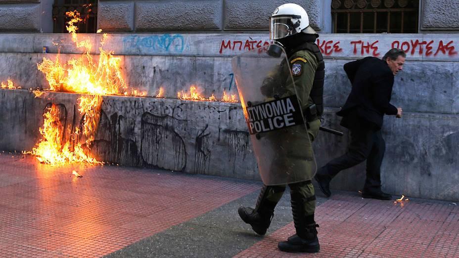 Policial passa próximo de fogo provocado por um coquetel molotov jogados por manifestantes em Atenas