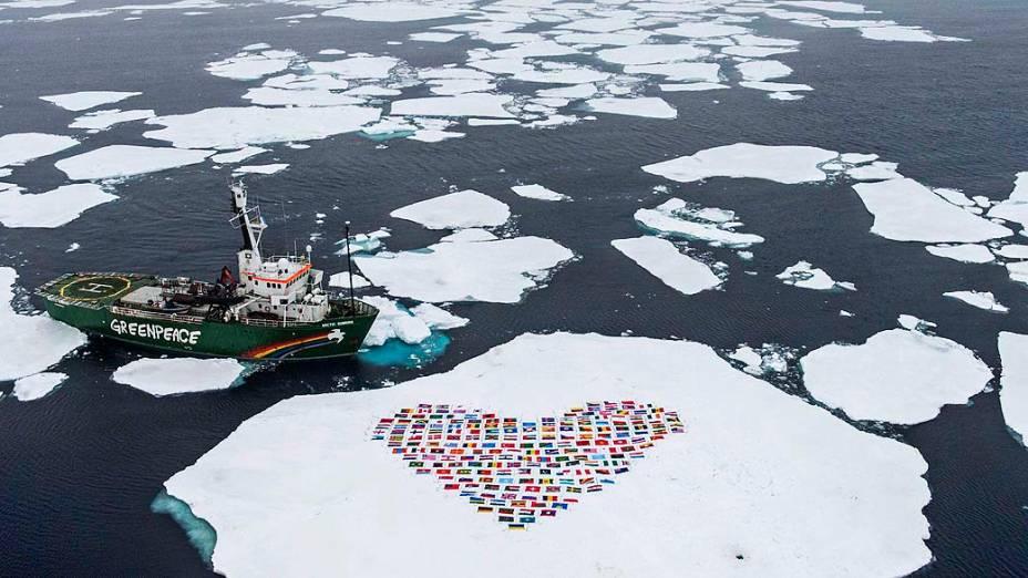 """Bandeiras dos 193 países que integram a ONU são colocadas na neve em frente navio Sunrise, do Greenpeace. A organização aproveitou a expedição """"Artic Sunrise"""" para apelar à ONU por medidas contra o degelo do Ártico"""