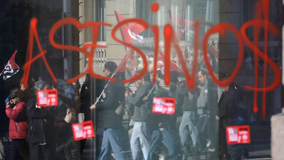 Manifestantes fazem pichação na porta de uma agência bancária em Madri durante a greve geral na Espanha