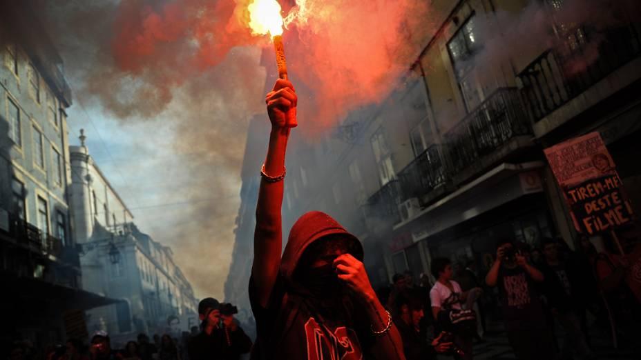 Manifestante segura tocha pelas ruas de Lisboa durante a greve geral em Portugal