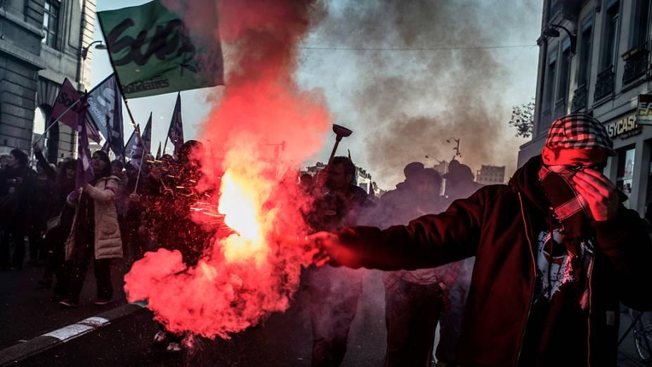 Manifestante segura tocha pelas ruas de Lyon durante a greve geral na França
