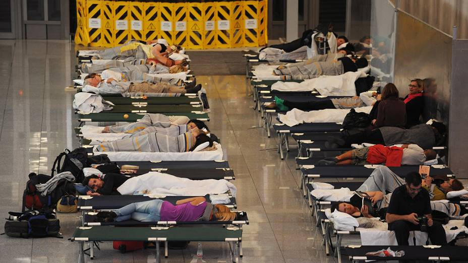 Passageiros dormem no aeroporto de Munique, durante greve de funiconários da Lufthansa na Alemanha