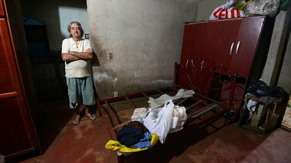A invasão de água e de esgoto destruiu móveis na casa da doméstica Raimunda. O vizinho Paulo Sérgio ajudou na retirada de poucos objetos da família