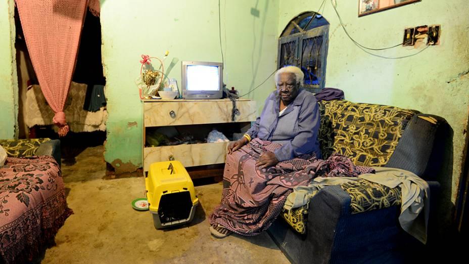Na parede da sala de Olga Coutinho, 80 anos, é possível ver a marca da água que invadiu a casa