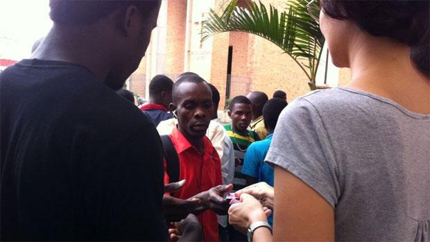 Imigrantes haitianos pegam senha para receber prato de comida no Centro Pastoral do Migrante, em São Paulo