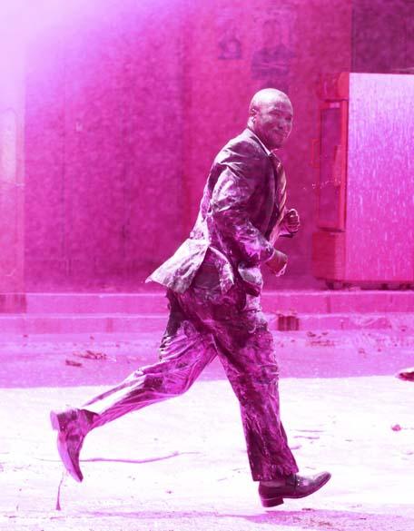 Manifestante durante conflito com a polícia na capital Campala, Uganda. Os policiais usaram gás lacrimogêneo e jatos de água colorida para dispersar os manifestantes que protestavam contra o governo