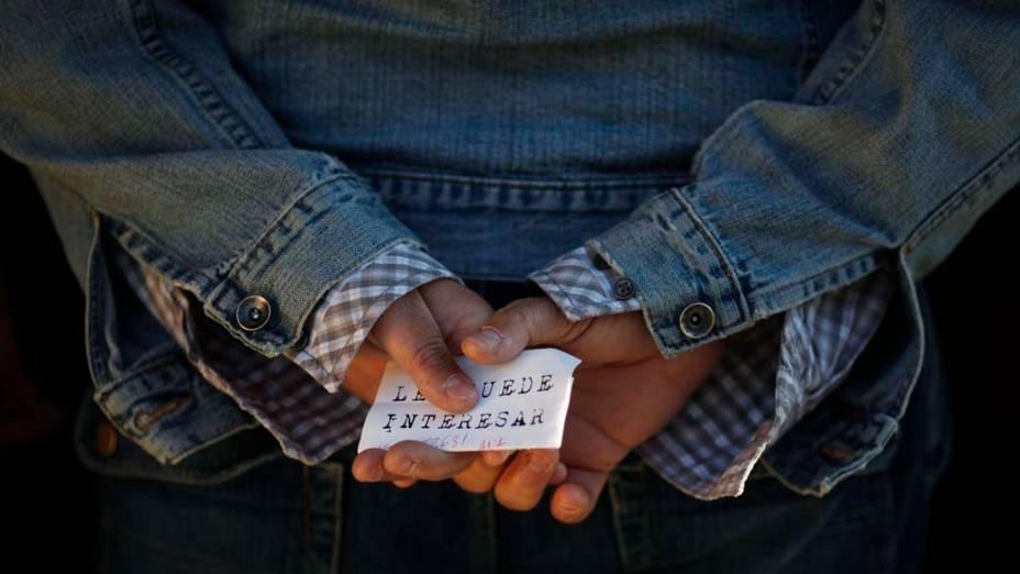 """Homem com folheto escrito """"Você pode se interessar"""", em fila de um centro para empregos na cidade de Málaga, Espanha"""