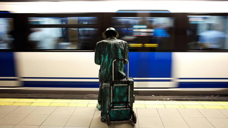 Homem vestido de estátua humana aguarda o metrô em Madri, Espanha