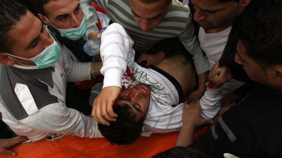 """Manifestante palestino atingido por gás lacrimogêneo disparado por soldados israelenses durante protestos na barreira de separação israelense no assentamento judaíco da Cisjordânia no """"Dia da Terra"""""""