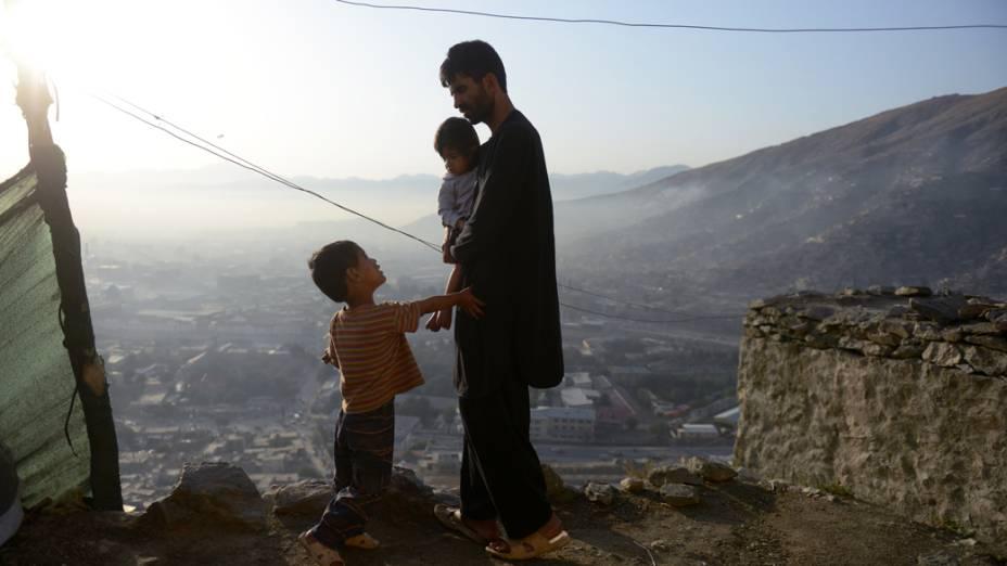 Construtor e seus filhos em frente sua casa em Cabul, Afeganistão