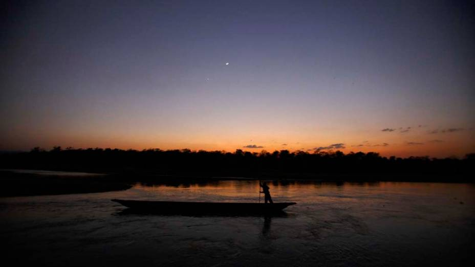 Homem em seu barco durante o pôr do sol no rio Rapti em Sauraha, Nepal