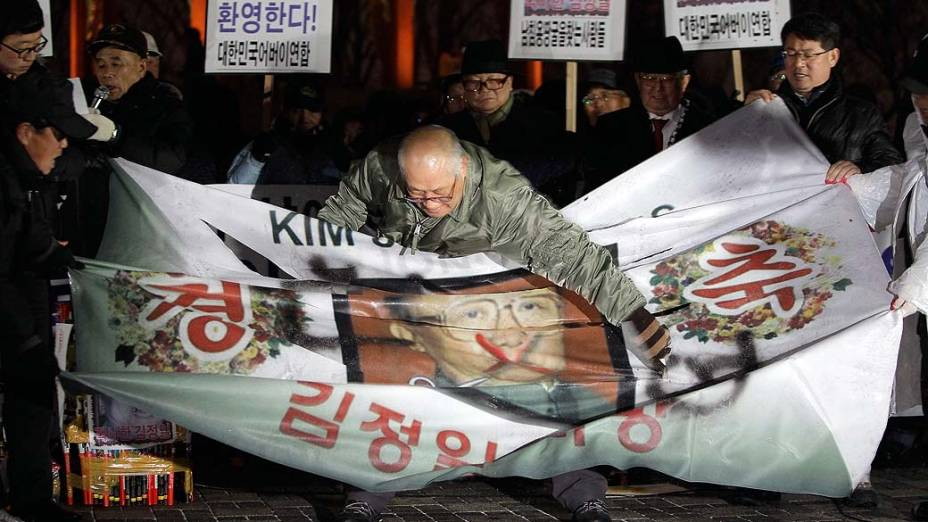 Em Seul, manifestantes rasgam retrato do falecido Kim Jong-Il durante um comício para celebrar a morte do líder norte-coreano, Coreia do Sul