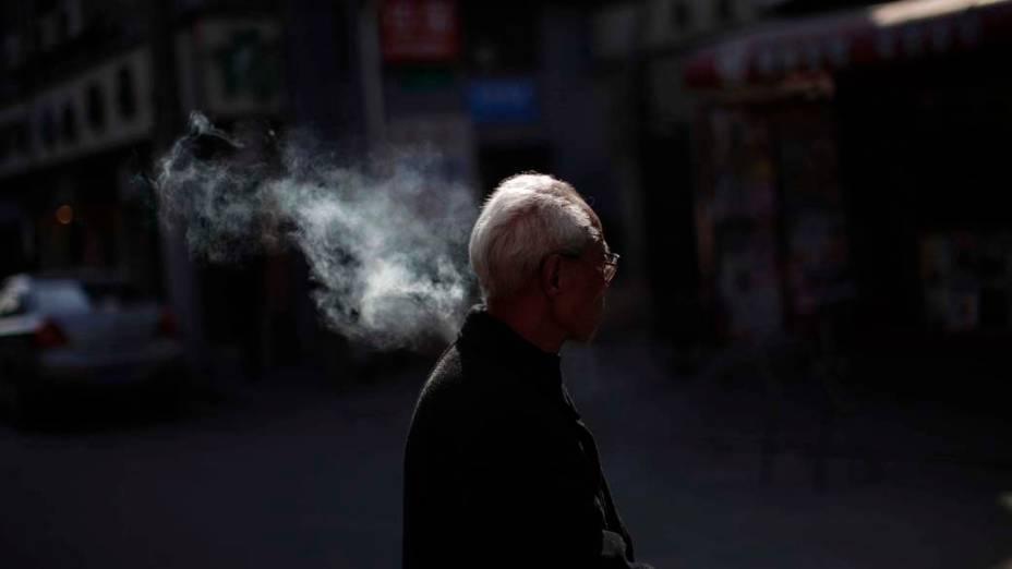 Homem fuma em rua de Shanghai, China