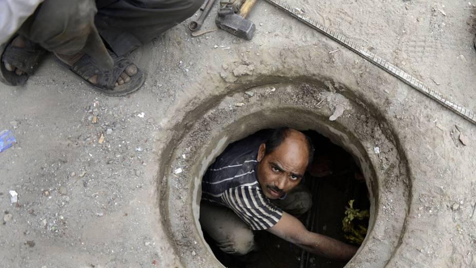 Encanador trabalha em tubulação subterrânea de Nova Délhi, na Índia