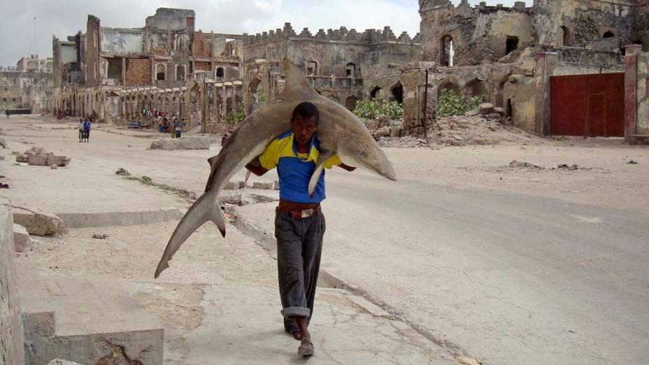 Homem carrega tubarão pelas rua de Mogadishu, Somália