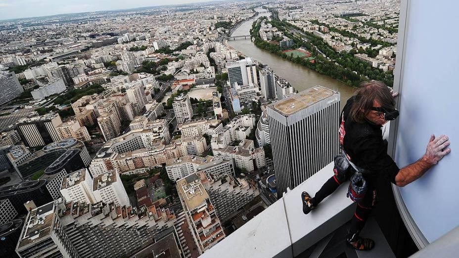 """O alpinista urbano Alain Robert, conhecido como o """"homem-aranha francês"""", escala o edifício Fist de 231 metros de altura; localizado no bairro financeiro de Paris, La Défense, o alpinista chegou no topo do arranha-céu em menos de uma hora"""