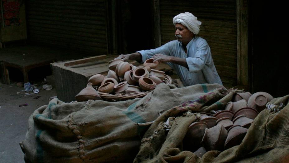 Vendedor arruma potes em mercado de Faisalabad, no Paquistão