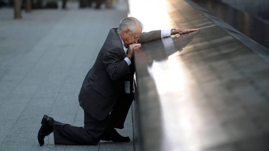 Robert Peraza ajoelha em frente ao nome do filho, Robert David Peraza, uma das vítimas do 11 de Setembro, em Nova York