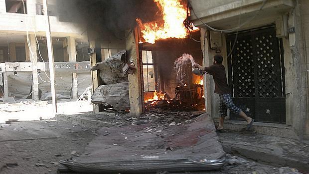 homem joga água em sua loja após a mesma ser incendiada em Homs, na Síria. Segundo ativistas, o Exército sírio continua bombardeando bairros de rebeldes no país