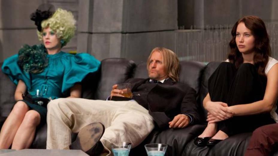Effie Trinket (Elizabeth Banks), à esquerda, é a responsável por fazer com que os tributos compareçam a todos seu compromissos; já Haymitch Abernathy (Woody Harrelson), ao centro, é o mentor de (Katniss Everdeen) Jennifer Lawrence, à esquerda, e Peeta Mellark (Josh Hutcherson) em Jogos Vorazes