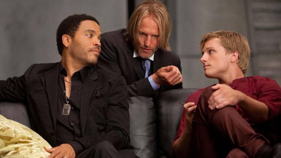 Cinna (Lenny Kravitzt), à esquerda, é o estilista pessoal de Katniss (Jennifer Lawrence); já Haymitch Abernathy (Woody Harrelson), ao centro, é o mentor dela e de Peeta Mellark (Josh Hutcherson), à direita