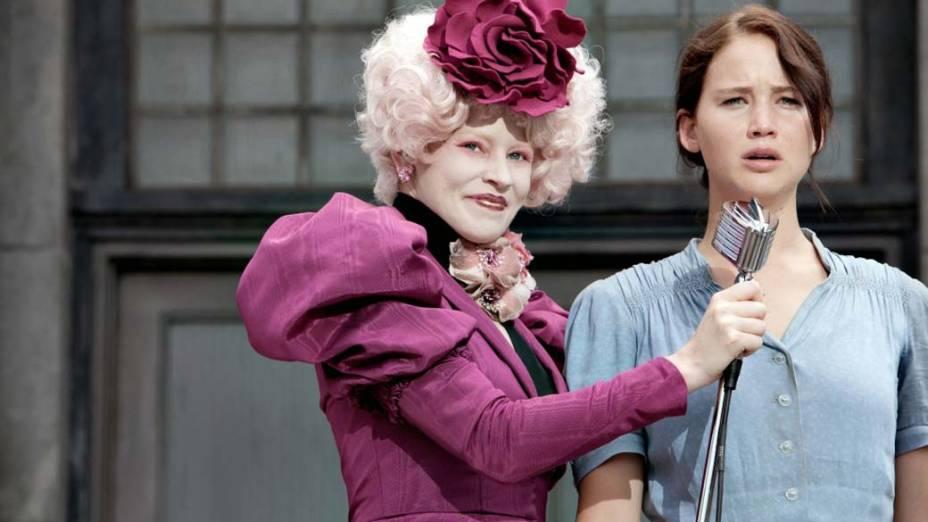 A extravagante Effie Trinket (Elizabeth Banks) é responsável por fazer com que todos os tributos, como Katniss Everdeen (Jennifer Lawrence), compareçam aos compromissos dos Jogos Vorazes
