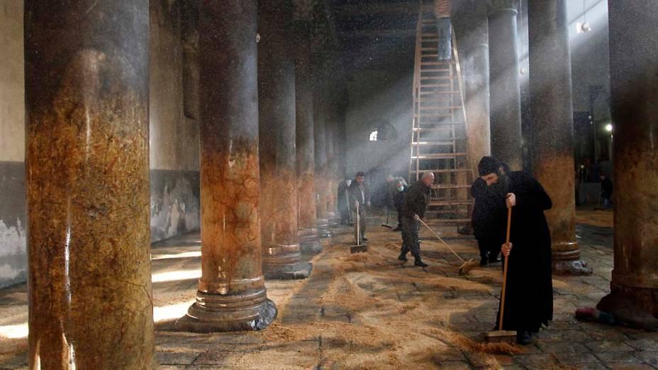 Grego ortodoxo e clérigo armênio limpam a Igreja da Natividade em Belém, Cisjôrdania