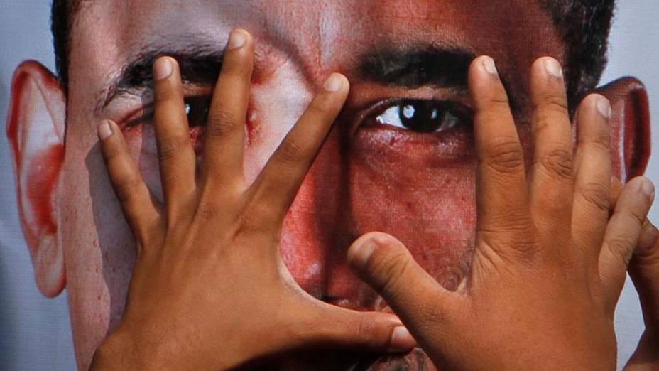 Imagem de Barack Obama coberta pelas mãos de partidários do movimento anti-americano em Hyderabad, no Paquistão