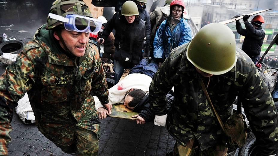 Manifestantes antigovernistas socorrem um companheiro ferido durante confrontos com a polícia na praça da Independência, em Kiev (Ucrânia)