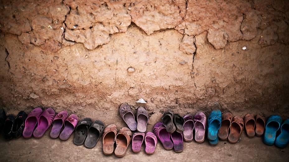 Sapatos pertencentes a crianças refugiadas afegãs são deixados do lado de fora de uma mesquita durante um evento por ocasião do Dia Mundial das Nações Unidas de justiça social, em uma escola improvisada na periferia de Islamabad, no Paquistão