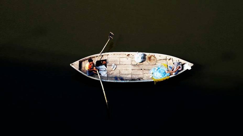 Pescador é fotografado nas águas sagradas do rio Ganes, em Allahabad, na Índia