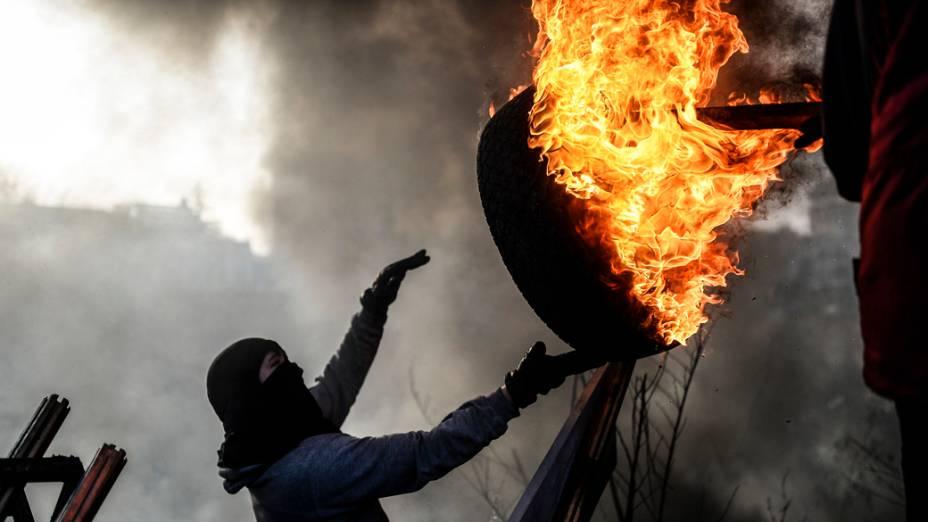 Manifestante arremessa pneu em chamas durante confrontos em Kiev, na Ucrânia