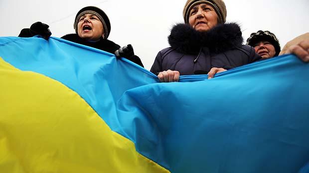 Em Simferopol, apoiadores pró-ucranianos carregaram uma grande bandeira do país em um protesto contra a integração da região de Crimeia à Rússia