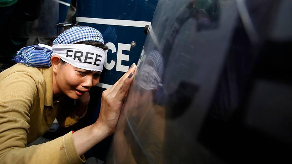 Manifestante chora durante confrontos com policiais em frente à Corte Municipal de Phnom Penh, no Camboja. Grupo exige a libertação de manifestantes presos após um protesto por melhores condições de trabalho em janeiro
