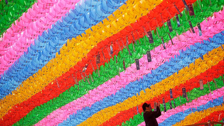 Homem amarra pedidos de oração, com nomes escritos em cartões, em lanternas de lótus, na preparação para o próximo aniversário de Buda no templo Jogye em Seul, Coreia do Sul