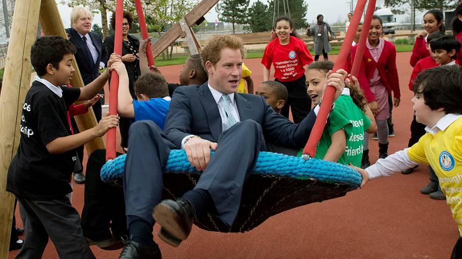 O príncipe Harry brinca com crianças em balanço durante visita ao Elizabeth Olympic Park antes de sua abertura em Stratford, no leste de Londres