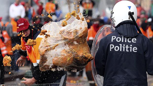 Manifestante atira saco cheio de lixo em policial durante manifestação em Bruxelas, na Bélgica, nesta sexta-feira (04)