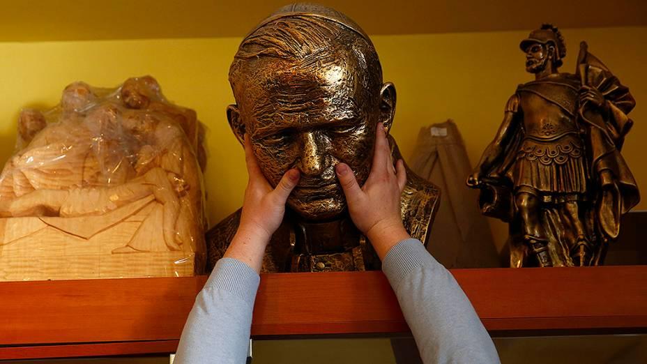 Vendedor segura um busto do falecido papa João Paulo II em uma loja na cidade de Kielce, no sul da Polônia