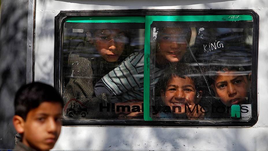 Um grupo de crianças reage à câmera enquanto viaja em um carro na cidade de Merhama, na Índia