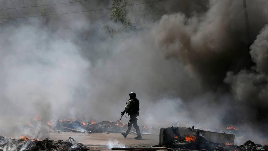 Oficial da força de segurança ucraniana caminha em um posto incendiado e deixado por separatistas pró-Rússia perto de Slaviansk, na Ucrânia