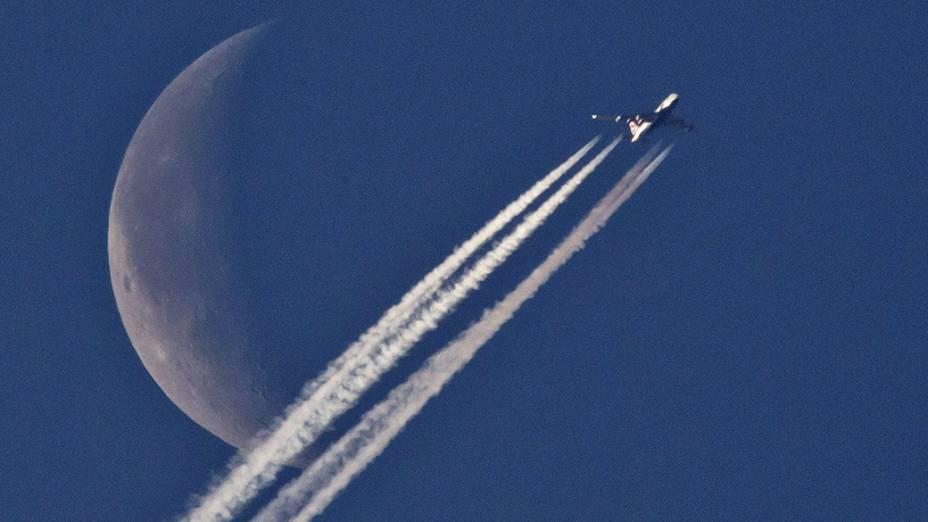 Avião sobrevoa a cidade de Nuremberg na Alemanha com a lua ao fundo
