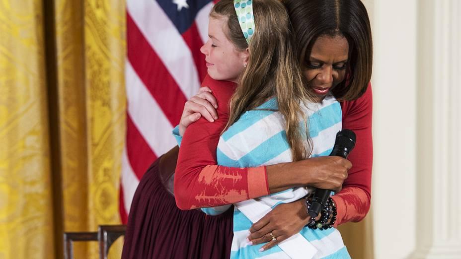 Menina entrega currículo de pai desempregado a Michelle Obama em evento na Casa Branca, nesta quinta-feira (24)