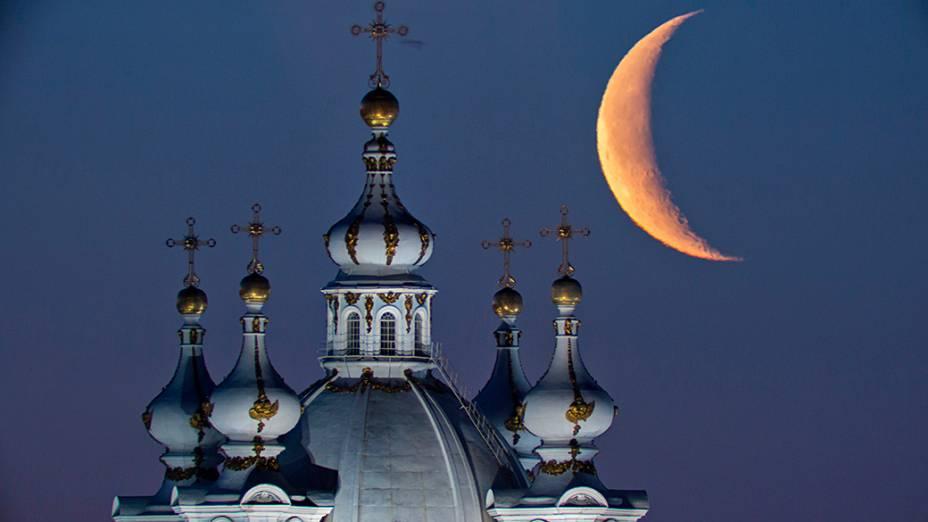 A lua vista acima das cúpulas da Catedral Smolny em São Petersburgo, na Rússia