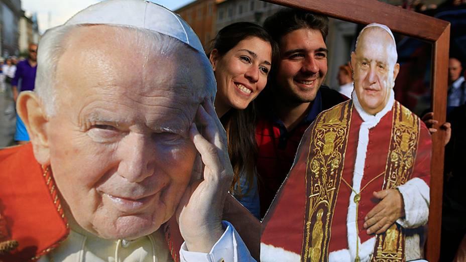 Em Roma, fiéis posam com fotos dos Papas João Paulo II e João XXIII que serão canonizados em cerimônia no próximo domingo