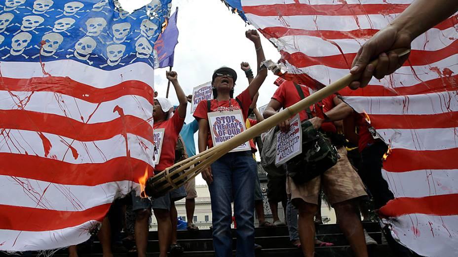 Ativistas queimam réplica gigante da bandeira dos Estados Unidos durante protesto em Manila, nas Filipinas, nesta sexta-feira (25)